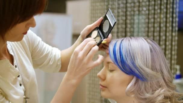 Profesionální make-up osoba mladá dívka s modrými vlasy