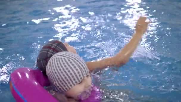 Wasserspiele für Kinder im Pool. Kleine Kinder baden im Schwimmbad