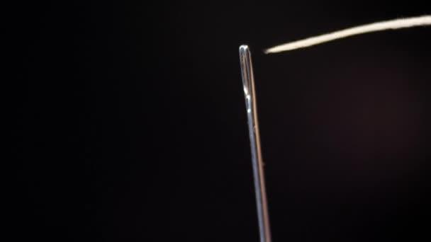 das Nadelöhr einfädeln. Den Faden in das Nadelöhr der Nähnadel ziehen.