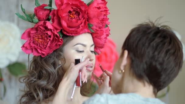 Make-up artist kadeřnice pracuje s modelem. stylista kreslí obrys rtů modely s červenou tužkou