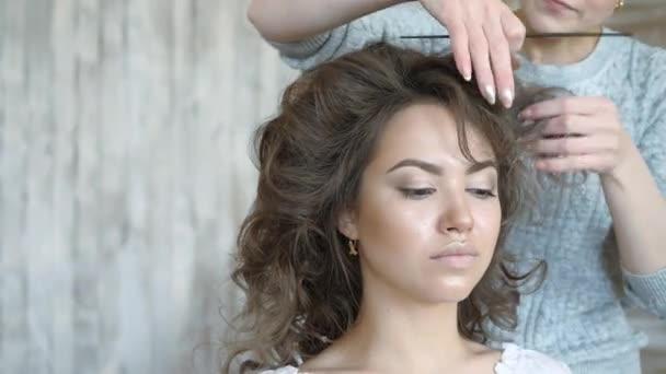 Make-up artist kadeřnice pracuje s modelem. Kadeřník dělá vlasový styling modelu. kadeřnice vytvoří svazek na vlasy modelu s hřebenem