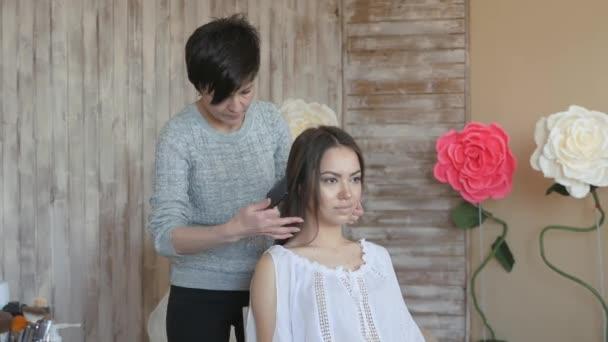 Make-up artist kadeřnice pracuje s modelem. Kadeřník dělá vlasový styling modelu. Žena je česání dlouhé tmavé vlasy, mladé dívky
