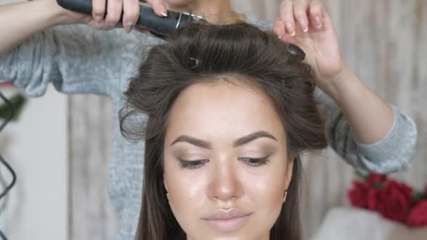 Make-up artist kadeřnice pracuje s modelem. Kadeřník dělá vlasový styling modelu. žena pracuje styler s dlouhými vlasy dívky. Kadeřník dělá kadeře na rovné vlasy dívky.