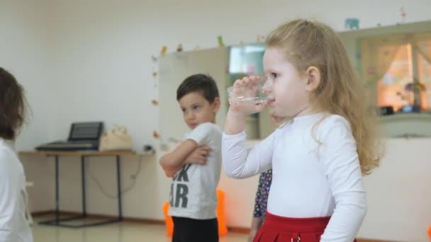 Çocuk Oyun Odası geliştirmek. Sınıflar eğlenceli sırasında duygular genç çocuk. sarışın kıvırcık çocuk içme suyu şeffaf cam olduğunu.