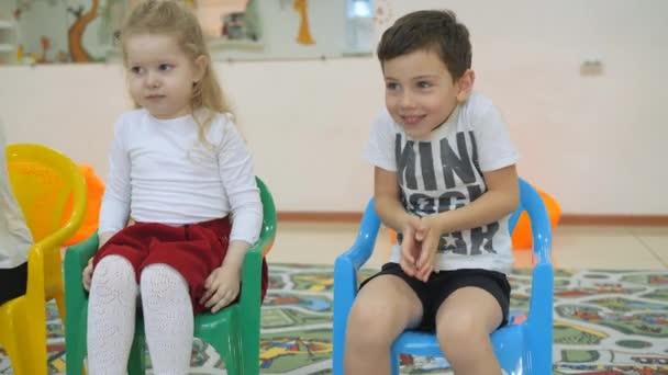 Lo Sviluppo Di Una Sala Giochi Per I Bambini Emozioni Dei Bambini Piccoli Durante Lezioni Divertenti I Bambini Si Siedono Sulle Sedie In Fila Il Bambino Sta Costruendo Unespressione Allegra