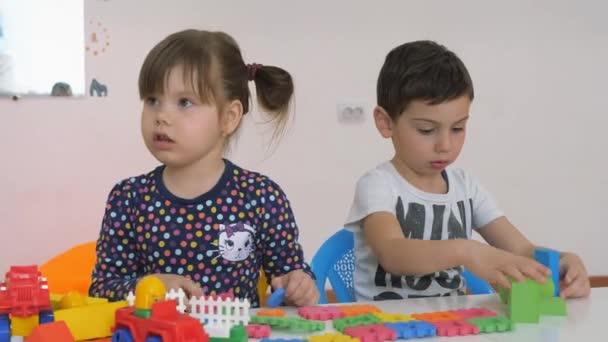 Lo Sviluppo Di Una Sala Giochi Per I Bambini Emozioni Dei Bambini Piccoli Durante Lezioni Divertenti Ragazzi E Ragazze Stanno Giocando Con Blocchi Di Legno Che Si Siede Al Tavolo