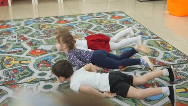 Childrens developing a game room. Emotions of young children during entertaining classes. Children cheerfully crawl on the stomach on the floor without the help of hands.
