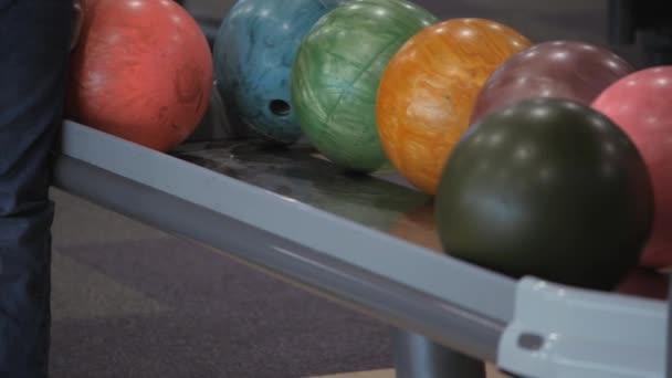 Zábava v bowlingu. Bruslení míče na trati s cílem srazit kolíky.