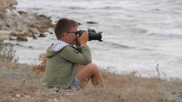 Letní prázdniny na pláži. Chlapec na pláži s kamerou. Vlny se lámou na břehu.