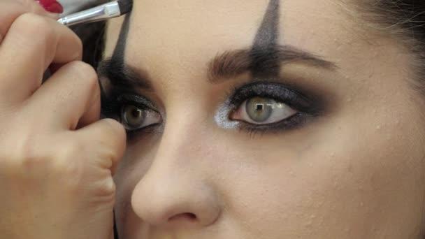 Könnyű Halloween smink. Egy lány egy szépségszalonban. Stílusos minta alkalmazása a modell arcán. Egy mester stylist munkája..
