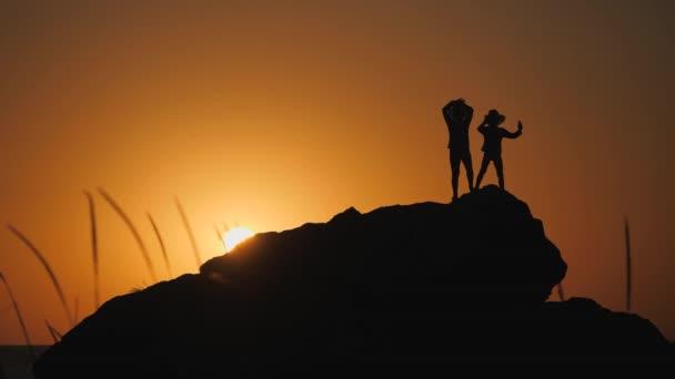 Silhouette per bambini contro il tramonto. Ragazzi in cappelli con brims stare su una roccia. La pietra si trova sulla riva del mare. Il sole tramonta dietro lorizzonte. Bambini che agitano le mani.