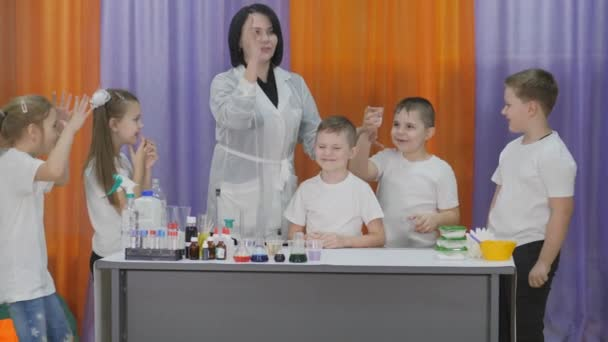 Chemical experiments for children. Boy pours a liquid for a chemical experiment into a plastic Cup with powder. Child tries to pour water on the boys head. Fun experiments for children. Woman pours