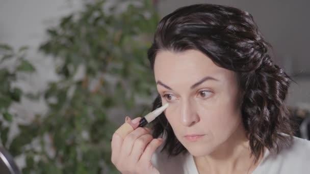 Kihasználom a reggeli sminket. A barna nő készít magának egy arcrajzot, mielőtt munkába megy. Az archang beállítása. Alkalmazza por a bőr körül a szem segítségével egy smink ecset.