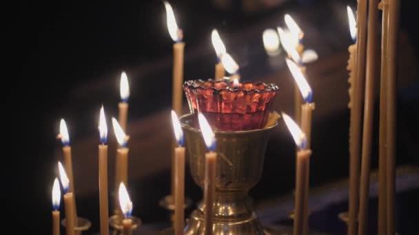 Pravoslavná tradice. Hořící svíčky na stojanu kolem lampy.