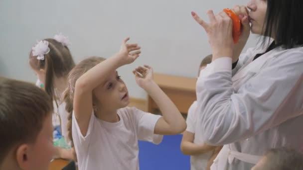 Chemische Experimente für Kinder. Die Menschen blasen elastische Blasen auf. Helle Emotionen der Kinder. Lustige Experimente für Kinder. Eine Frau leitet den kognitionswissenschaftlichen Unterricht. Fun Spiele für Kinder. Kinder stehen mit Geschirr für Chemikalien am Tisch.