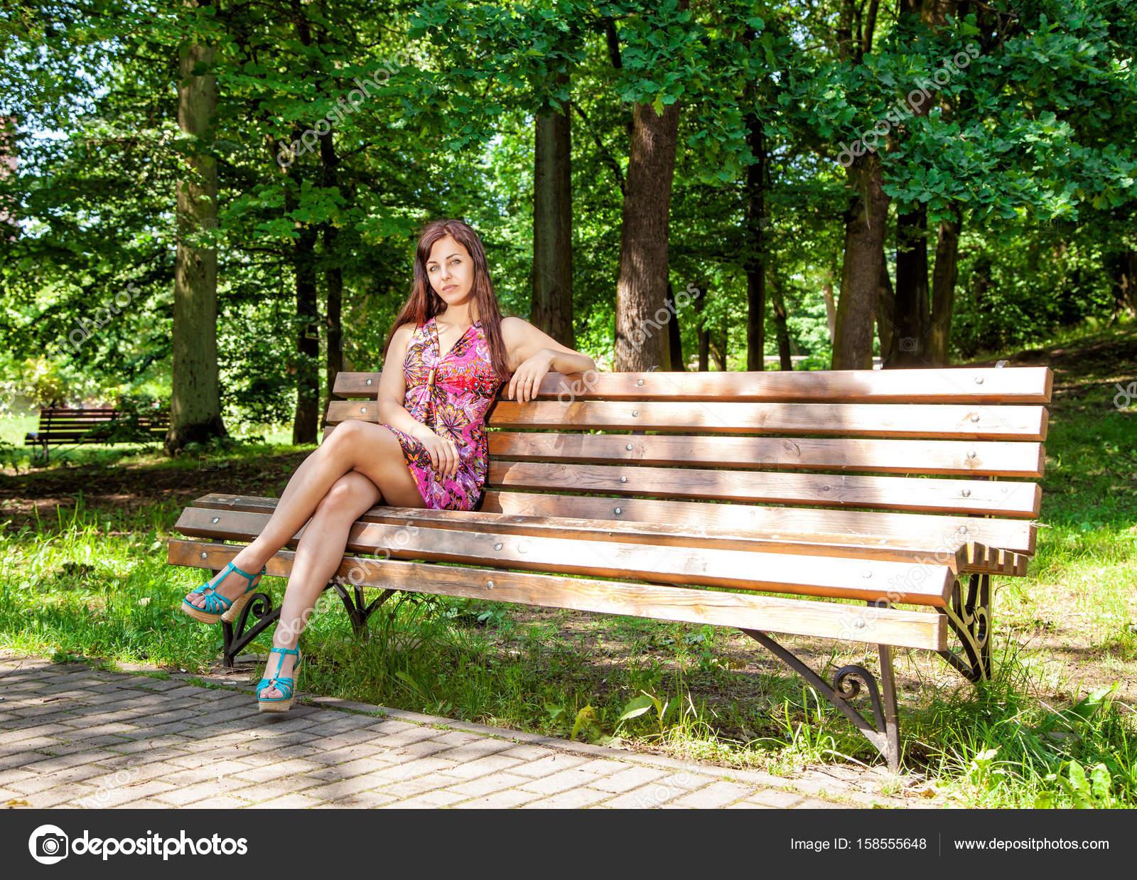 Jeune belle étudiante brune assise sur le banc avec