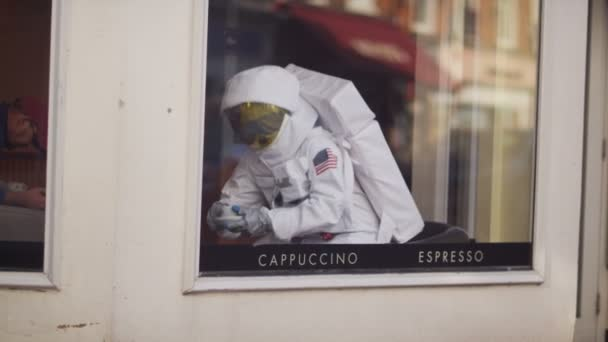 Astronaut with coffee sitting in coffee shop