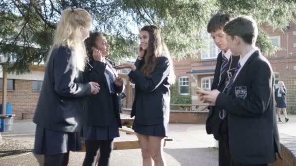 Školní děti používající mobilní telefony