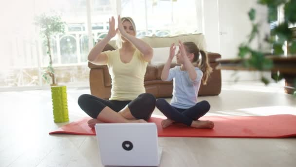 mother and daughter follow a yoga