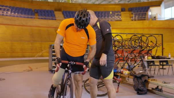 cyclist  practicing with trainer in velodrome