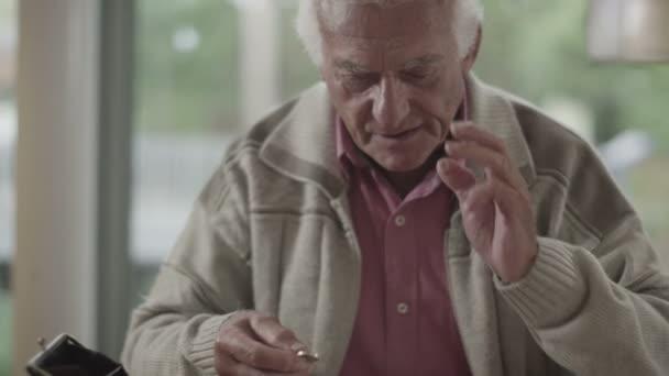 starší muž snaží počítat z mince