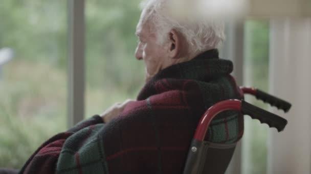 muž sedí u okna