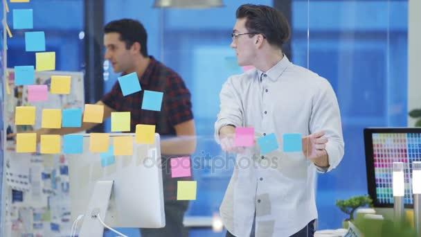 4 k mužské návrháři pracují společně v kreativní office pomocí poznámek sticky notes