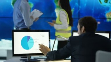 4K Business team discussing large world map graphic on video wall, with pie charts and graphs displayed on computer screens