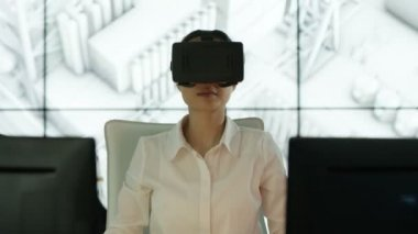 4K Engineer wearing virtual reality viewer at her desk with animated graphic of architectural structure in background
