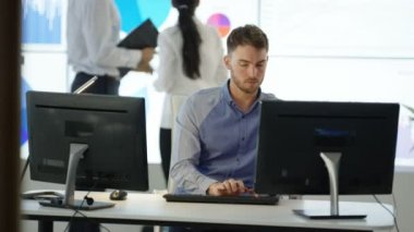 4K young businessman working on computer at his desk with colleagues looking at video wall in background