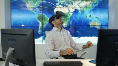 4K Businessman or gamer wearing virtual reality viewer at his desk with world map graphic in background