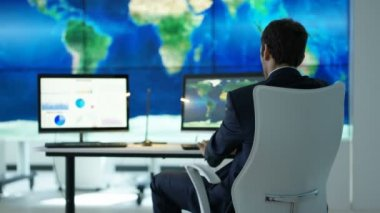 4K Businessman working in office with large world map graphic on video wall and pie charts and graphs displayed on computer screens