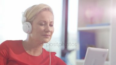 Woman relaxing at home, listening to music with headphones and tablet
