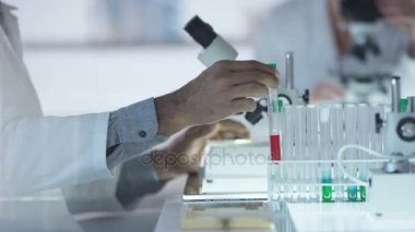 Medical researcher working in the lab analyzing samples under microscope