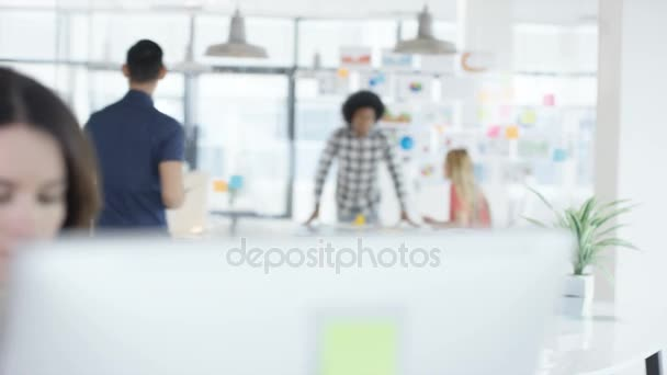 4K Young woman working on computer in creative office with colleagues talking in background