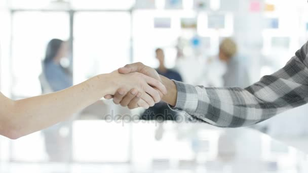 4K Close up on handshake of unrecognizable business people with colleagues having a discussion in background