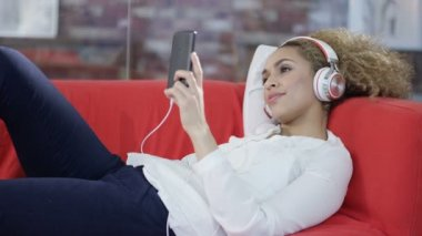 4K Attractive woman relaxing at home, listening to music with headphones and smartphone