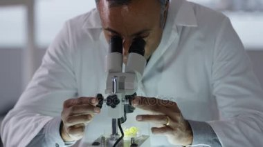 Portrait of smiling medical researcher working in the lab analyzing plant sample