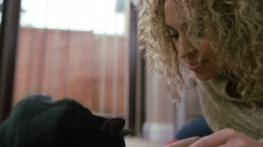 4K Close up of young woman playing with cute black kitten at home