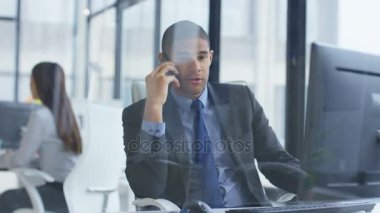 4K Stressed businessman talking on phone and working on computer in the office