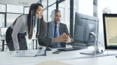 4K Business man and woman in the office discussing information on computer screen.