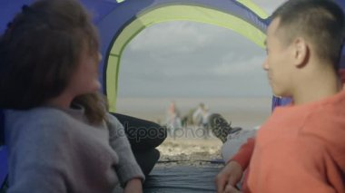 4K Young couple in tent at the beach relaxing while friends have fun outside