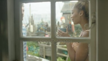 4K Young romantic couple at beach house, talking and looking out at the view