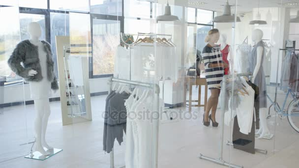 Beautiful pregnant woman looking at clothes in fashionable boutique store.