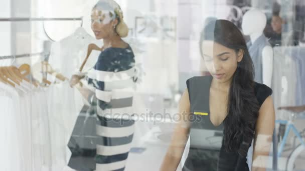 Female customers shopping and clerk giving assistance in fashionable boutique clothing store.