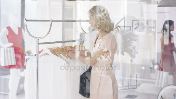 Beautiful female customer shopping in fashionable boutique clothing store.