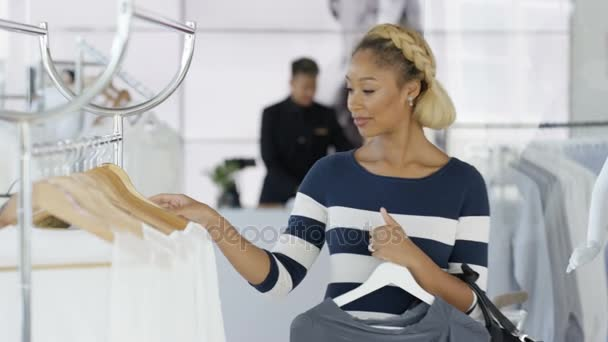 Beautiful female customers shopping in fashionable boutique clothing store.