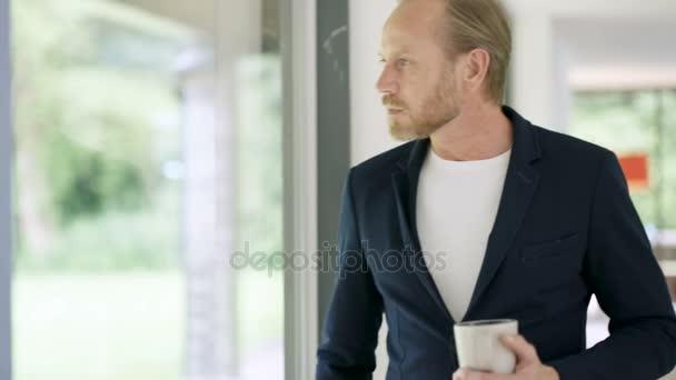 Portrét usmívajícího se muže v moderních domů, pití kávy vedle okna