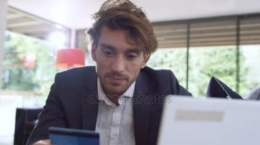 Attractive smartly  dressed man with credit card shopping online at home