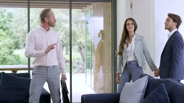 Šťastný pár s realitní agent, zobrazování moderních domů a třes rukou